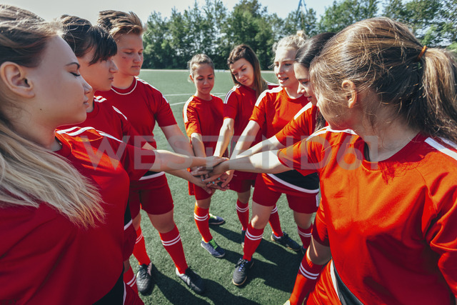 Close-up of sports team stacking hands on field - FSIF01754 - fStop/Westend61