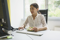 Businesswoman using computer while having salad at creative office - FSIF01778