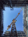 Directly below shot of crane amidst glass building against clear blue sky - FSIF01802
