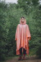 Portrait of woman wearing raincoat standing amidst plants during rainy season - FSIF01820