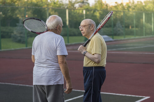 Senior friends carrying tennis rackets while talking at playing field - FSIF01832