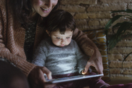 Mother and daughter using digital tablet at home - GEMF01885
