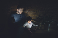 Father and daughter looking at   digital tablet at home in the dark - GEMF01888