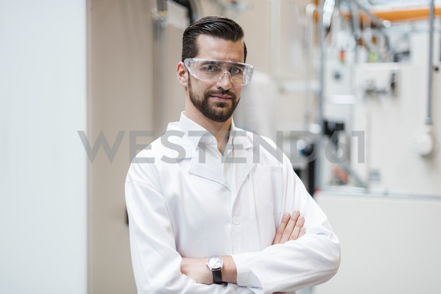 Portrait of man wearing lab coat and safety goggles in factory - DIGF03390