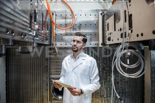 Man wearing lab coat and safety goggles at machine holding tablet - DIGF03393