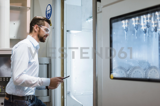 Businessman with tablet wearing safety goggles examining machine in factory looking - DIGF03396