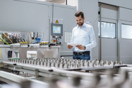 Businessman at machine in factory looking at tablet - DIGF03399