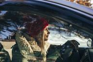 Woman in warm clothing driving car - FSIF01853