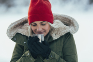Close-up of young woman having coffee while during winter - FSIF01856