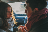 Young couple holding hands in car - FSIF01859