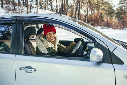 Portrait of smiling woman in warm clothing driving car - FSIF01865