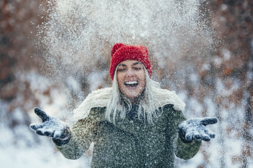 Happy young woman playing in snow - FSIF01868