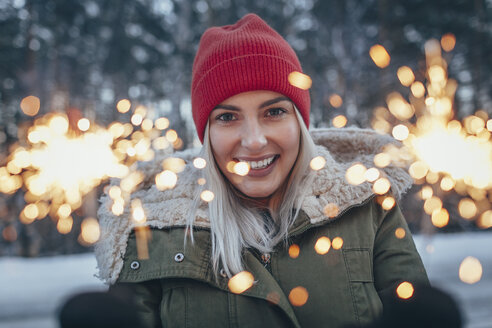 Portrait of smiling woman holding sparklers during winter - FSIF01874