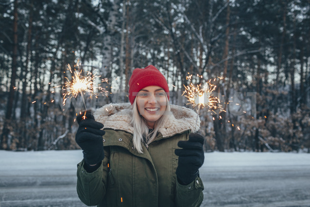 Smiling woman holding sparklers during winter - FSIF01877