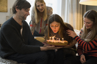 Family looking at young woman blowing out birthday candles at home - FSIF01928