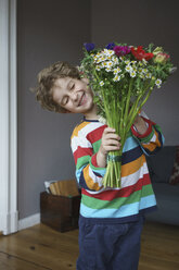 Happy boy holding bunch of flowers standing at home - FSIF01955