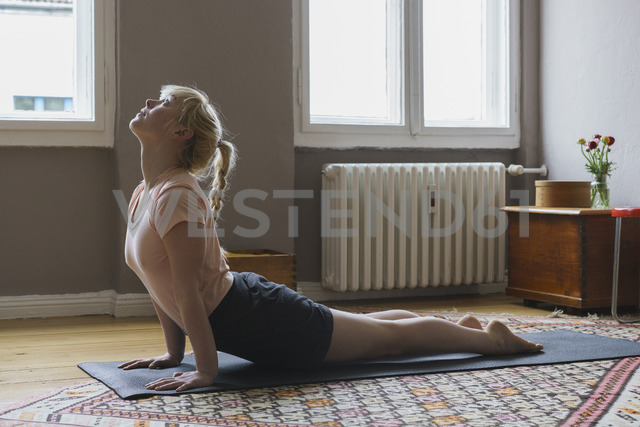 Side view of young woman performing yoga at home - FSIF01970