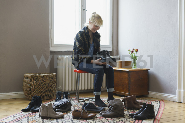 Happy woman holding shoes while sitting at home - FSIF01973 - fStop/Westend61
