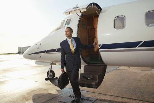 Businessman boarding a private airplane - FSIF02048