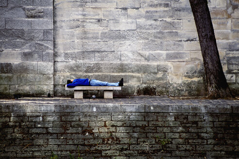 Man lying on a bench by the Seine, Paris, France - FSIF02060
