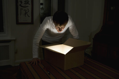 Young man staring into illuminated cardboard box - FSIF02108