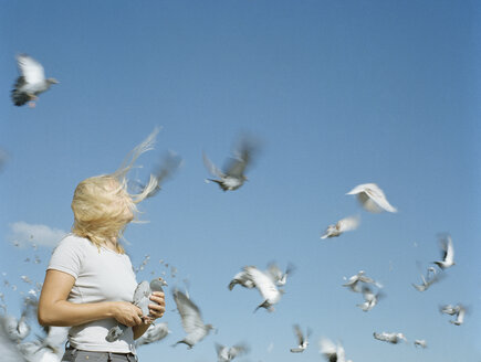 A woman holding a pigeon as other pigeons fly around her - FSIF02132