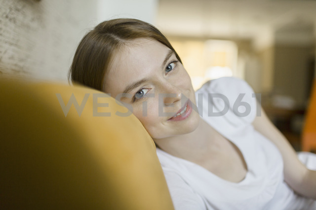 Portrait of smiling woman resting on sofa at home - FSIF02171