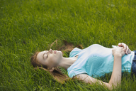 Young woman resting with eyes closed on grassy field - FSIF02174