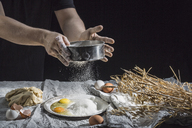 Midsection of man sprinkling flour over eggs at table - FSIF02177