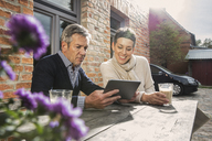 Mature couple sitting with digital tablet and coffee in back yard - FSIF02189