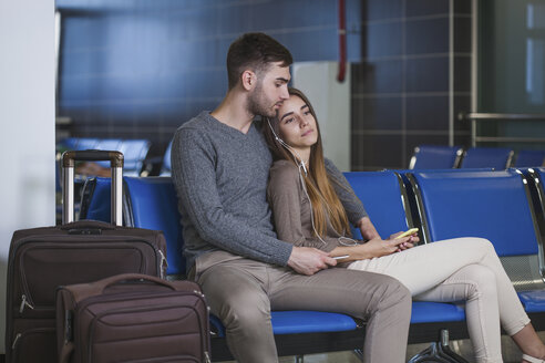 Young couple listening music through mobile phone while waiting in airport - FSIF02222