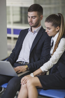 Young businesswoman sitting by businessman using laptop at airport - FSIF02225