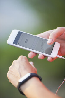Cropped image of woman using pedometer and mobile phone - FSIF02228