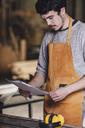 Carpenter reading document at workshop - FSIF02246