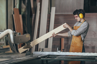 Carpenter examining plank of wood by table saw at workshop - FSIF02255