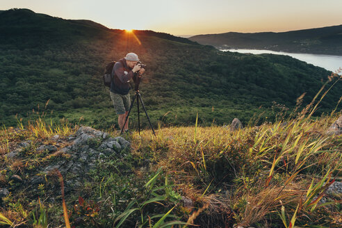 Man photographing on grassy field during sunset - FSIF02264