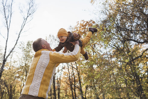Low angle view of cheerful man lifting baby boy at park during autumn - FSIF02267