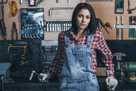 Portrait of female mechanic standing at workshop - FSIF02270