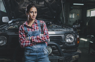 Portrait of confident female mechanic with arms crossed leaning on car at workshop - FSIF02273