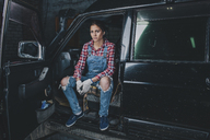 Portrait of confident female mechanic sitting in car at workshop - FSIF02276