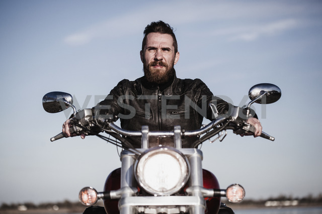 Portrait of confident biker sitting on motorcycle against sky - FSIF02291