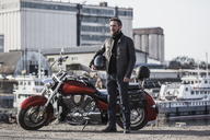 Full length portrait of biker holding helmet while standing by motorcycle against industrial setting - FSIF02294