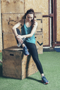 Full length of female athlete holding water bottle while sitting on wooden box at gym - FSIF02309