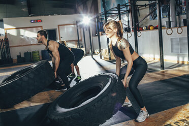 Determined male and female athletes flipping tire at health club - FSIF02312