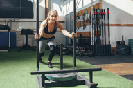 Determined woman doing sled push exercise at health club - FSIF02315