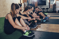 Male and female athletes talking while sitting on carpet at gym - FSIF02318