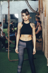 Portrait of confident sportswoman standing at gym with friends in background - FSIF02321