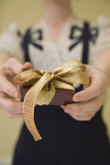 Young woman holding a present - FSIF02336