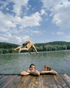 A young man diving into a lake with friends - FSIF02363