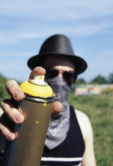 A man holding a can of spray paint - FSIF02405